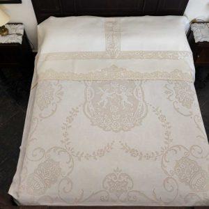 copriletto e lenzuolo realizzati con tecnica dello sfilato con motivo vasi ed angeli